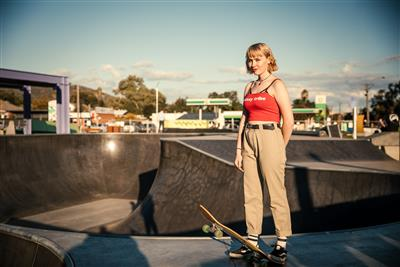 Girl standing on side of skate bowl with skate board